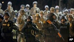 Police and Missouri National Guardsmen stand guard as protesters gather in front of Ferguson Police Department in Ferguson, Nov. 28, 2014.
