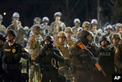 FILE - Police and Missouri National Guardsmen stand guard as protesters gather in front of the police department in Ferguson, Nov. 28, 2014.