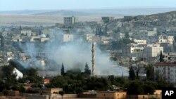 Asap mengepul dari kota Kobani akibat pertempuran antara pejuang Kurdi melawan militan ISIS (19/10).