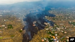 Lava from a volcano eruption flows destroying houses on the island of La Palma in the Canaries, Spain, Sept. 21, 2021.