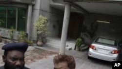 图为一名巴基斯坦警察与另一人8月15日站在被绑架美国专家在拉合尔的住宅外