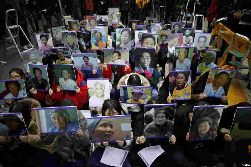 "Students hold portraits of deceased former South Korean ""comfort women"" during a weekly anti-Japan rally in front of the Japanese embassy in Seoul, South Korea."
