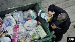 Một người đàn ông kiếm thức ăn từ một thùng rác tại Hy Lạp