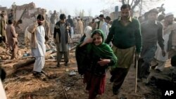 A Pakistani girl whose father is injured in a car bomb blast which killed many people, walks at the site of explosion in suburbs of Peshawar, Pakistan, February 02, 2011.