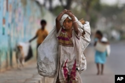 A girl collecting reusables walks in Hyderabad, India, March 9, 2016. Child labor remains widespread in India, where an estimated 13 million children work, with laws meant to keep kids in school and out of the workplace routinely flouted.
