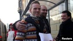 Thành viên thủy thủ đoàn tàu Arctic Sunrise, Mannes Ubels (trái) đang cầm những văn bản chứng nhận quyết định bãi bỏ khởi tố sau khi ông rời khỏi văn phòng Bộ Dịch vụ Di trú Liên bang ở St. Petersburg, 25/12/2013