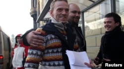 Greenpeace ship Arctic Sunrise crew member Mannes Ubels (L, front) holds papers certifying the termination of prosecution after he walked out of the offices of the Federal Migration Service Department in St. Petersburg, Dec. 25, 2013.