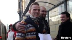 Para aktivis Greenpeace usai mendapatkan amnesti dari pemerintah Rusia keluar dari tempat penahanan mereka di St. Petersburg, Rabu (25/12).