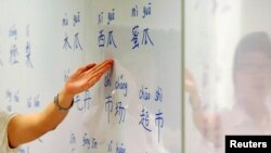 FILE - An instructor points out Mandarin characters on a whiteboard at a night class for people learning Mandarin as a second language in Singapore, Sept. 1, 2009.