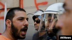 Član radničkog sindikata PAME raspravlja se sa policijom na protestu protiv mera štednje u centru Atine, 3. jula 2015.