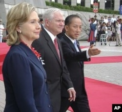 US Secretary of State Hillary Clinton and Secretary of Defense Robert Gates with South Korean Defense Minister Kim Tae-Young prepare to greet visitors at the Korean War Memorial in Seoul, 21 July 2010