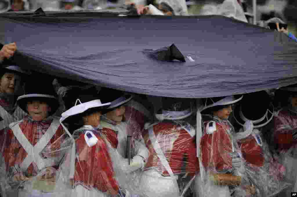 'Tamborilleros' wearing their uniform shelter from the rain, march in the traditional ' La Tamborrada', during 'El Dia Grande', the main day of San Sebastian feasts, in the Basque city of San Sebastian, northern Spain.