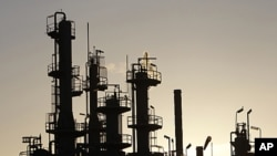 Towers and smokestacks are silhouetted at an oil refinery in Melbourne (2010 file photo)