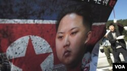 Park Sang Hak ຜູ້ໂຕນໜີຈາກເກົາຫລີເໜືອ (ຂວາ) ກໍາລັງຖືປ້າຍປະທ້ວງ ຕໍ່ຕ້ານຜູ້ນໍາເກົາຫລີເໜືອ ທ່ານ King Jong Un.
