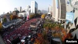 """ປະຊາຊົນ ເກົາຫຼີໃຕ້ ຮ້ອງຄຳຂວັນ ແລະ ຖືປ້າຍທີ່ອ່ານວ່າ """"Park Geun-hye Out"""" ໃນລະຫວ່າງການປະທ້ວງຕໍ່ຕ້ານ ປະທານາທິບໍດີ ເກົາຫຼີໃຕ້ ທ່ານນາງ Park Geun-hye ໃນນະຄອນຫຼວງ ໂຊລ, 12 ພະຈິກ, 2016."""