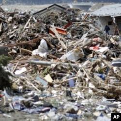 A survivor walks through debris in Rikuzentakata, Iwate prefecture, where the earthquake and tsunami hit last week, March 18, 2011