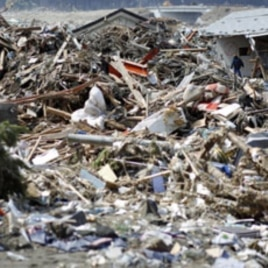 A survivor walks through debris in Rikuzentakata, Iwate prefecture, where the earthquake and tsunami hit last week, March 18, 2011