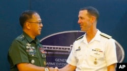 Philippine Armed Forces Chief Gen. Carlito Galvez Jr., left, and Adm. John Richardson, chief of Naval Operations of the U.S. Navy, shake hands prior to a news conference following their meeting at Camp Aguinaldo in suburban Quezon city, northeast of Manila.