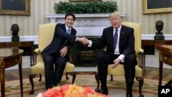 Presiden AS Donald Trump (kanan) berjabat tangan dengan tamunya, PM Kanada Justin Trudeau di Gedung Putih, Senin (13/2).