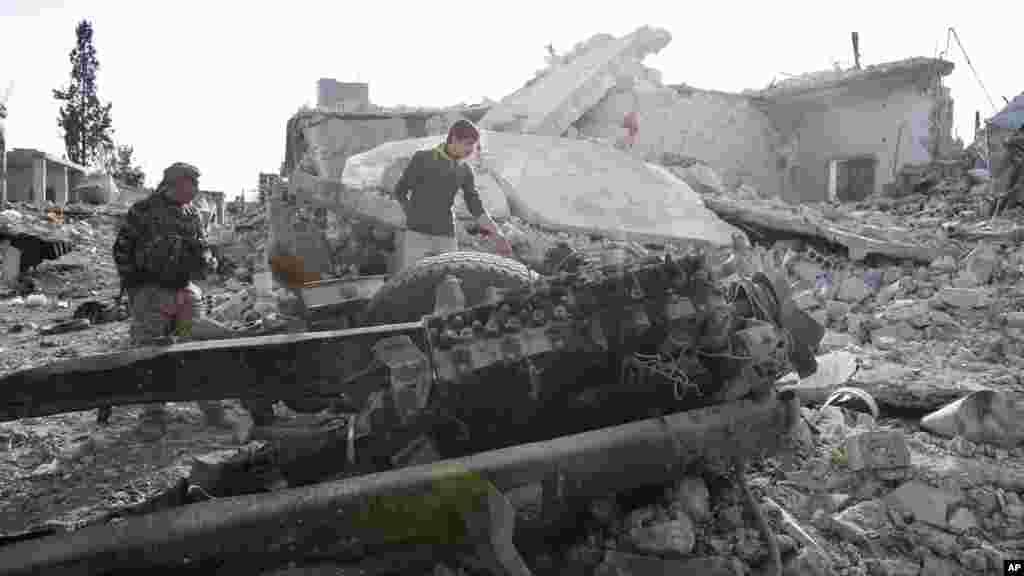 Des combattants kurdes montrent les dommages causés par un camion piégé dans Kobani, le 19 novembre 2014.