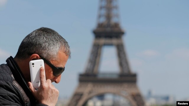 A man makes a phone call using his mobile phone at the Trocadero Square near the Eiffel Tower in Paris, May 16, 2014.