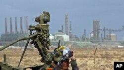 3月8日一名反政府士兵在一座炼油厂前准备抗击卡扎菲部队的空袭