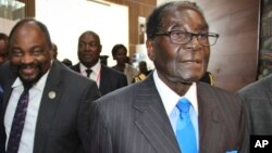 FILE: Zimbabwe's President Robert Mugabe, right, arrives for the heads of state meeting of the annual African Union (AU) summit, held at the AU headquarters in Addis Ababa, Ethiopia, Jan. 30, 2015.