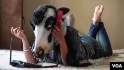 گائے کے ماسک میں ایک خاتون فون پر مصروف۔