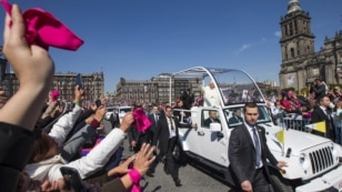 In this photo provided by the office of the Mexican president, Pope Francis waves to the crowd from the popemobile on Zocalo Square in Mexico City, Feb. 13, 2016.