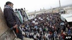 Một thành viên của lực lượng Quân đội Giải phóng Syria canh gác trong lúc người biểu tình xuống đường tại Idlib, ngày 6/2/2012