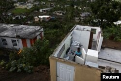 Ernestina Lebron looks at her refrigerator in her home in Maunabo, Jan. 27, 2018.