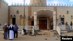 People stand outside Al Rawdah mosque, where a bomb exploded, in Bir Al-Abed, Egypt, Nov. 25, 2017.