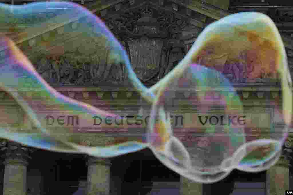"Soap bubbles float past the lettering ""Dem Deutschen Volke"" (To the German People) written on the Reichstag building housing the Bundestag (lower house of parliament) in Berlin, Sept. 22, 2013."
