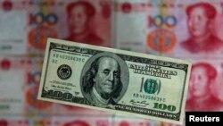 100元人民币衬托下的100美元纸币。