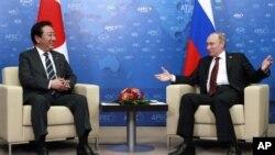 지난 9월 아시아태평양경제협력체(APEC) 정상회의에서 대화중인 노다 요시히코 일본 총리(왼쪽)와 블라디미르 푸틴 러시아 대통령. (자료사진)