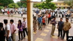 Cambodians wait on a line before they vote at a polling station in Phnom Penh, Cambodia, Sunday, July 27, 2008.