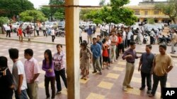 Cambodians wait on a line before they vote at a polling station in Phnom Penh, file photo.