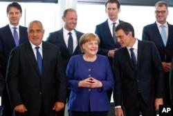 La canciller alemana Angela Merkel (centro), habla con el primer ministro español, Pedro Sánchez, mientras posan para una foto grupal en una cumbre informal de la UE sobre migración en la sede de la UE en Bruselas, el domingo 24 de junio de 2018. (Yves Herman, Pool Photo vía AP).