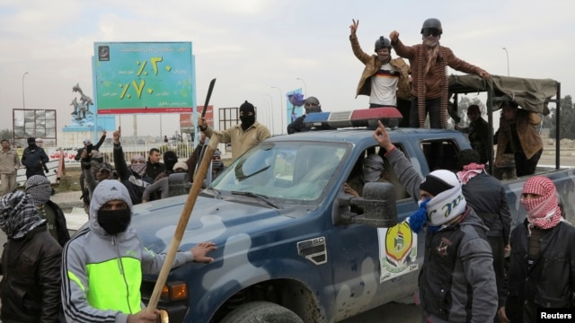 Gunmen takeover a police vehicle in Ramadi, Iraq, Dec. 30 2013.