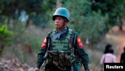 A soldier walks during Myanamar vice-president Sai Mauk Kham (not pictured) visit to a school to meet with government workers who fleet from Laukkai, in Lashio, Feb. 20, 2015.