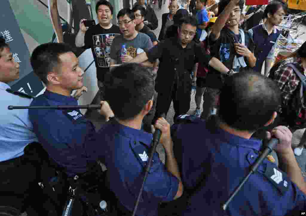 Riot police officers stop the pro-democracy protesters from reoccupying the area in the Mong Kok district of Hong Kong, early Friday, Oct. 17, 2014.