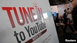 Les visiteurs passent devant un stand YouTube pendant le marché international de l'édition de musique d'enregistrement et de la musique vidéo (MIDEM) à Cannes, France, le 27 janvier 2013.