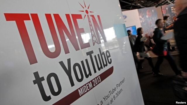 Visitors walk past a YouTube stand during the International Record Music Publishing and Video Music Market (MIDEM) in Cannes, France, Jan. 27, 2013.