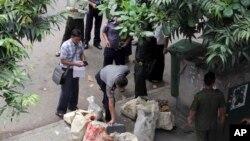 Seorang polisi memeriksa dengan seksama paket mencurigakan yang ditemukan oleh petugas penjinak bom di pusat kota Rangoon, Burma, 15 Oktober 2013 (Foto: dok).
