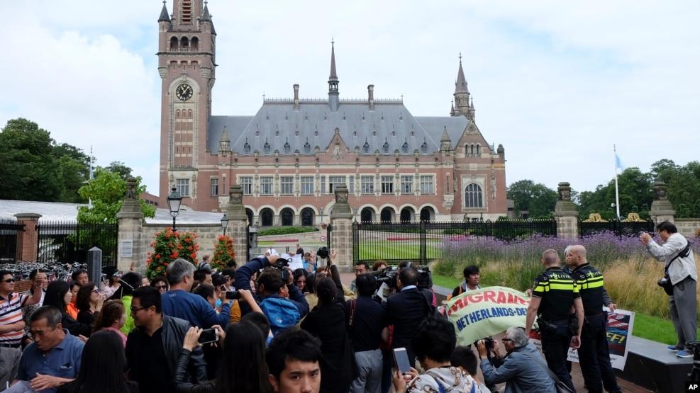 Người biểu tình, cảnh sát, và phóng viên tập trung bên ngoài Cung điện Hòa bình ở La Haye, Hà Lan, 12/7/2016, trước phán quyết của Tòa Trọng tài LHQ về tranh chấp Biển Đông.