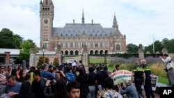 Demonstrators, police, and media gather outside the Peace Palace in The Hague, Netherlands, on Tuesday, July 12, 2016, ahead of a ruling by the Permanent Court of Arbitration (PCA) on the dispute between China and the Philippines over the South China Sea.