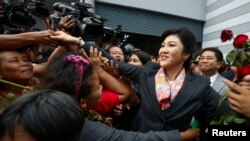 Thailand's Prime Minister Yingluck Shinawatra greets her supporters as she leaves the Permanent Secretary of Defence office in Bangkok May 7, 2014. A Thai court found Yingluck guilty of violating the constitution on Wednesday and said she had to step down