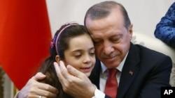 Presiden Turki Recep Tayyip Erdogan memeluk Bana Al-Abed, (7 tahun), di Istana Presiden di Ankara, Turki, Selasa (21/12).
