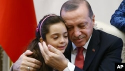 Turkey's President Recep Tayyip Erdogan, embraces Bana Al-Abed, 7, from Aleppo, Syria, at his Presidential Palace in Ankara, Dec. 21, 2016.