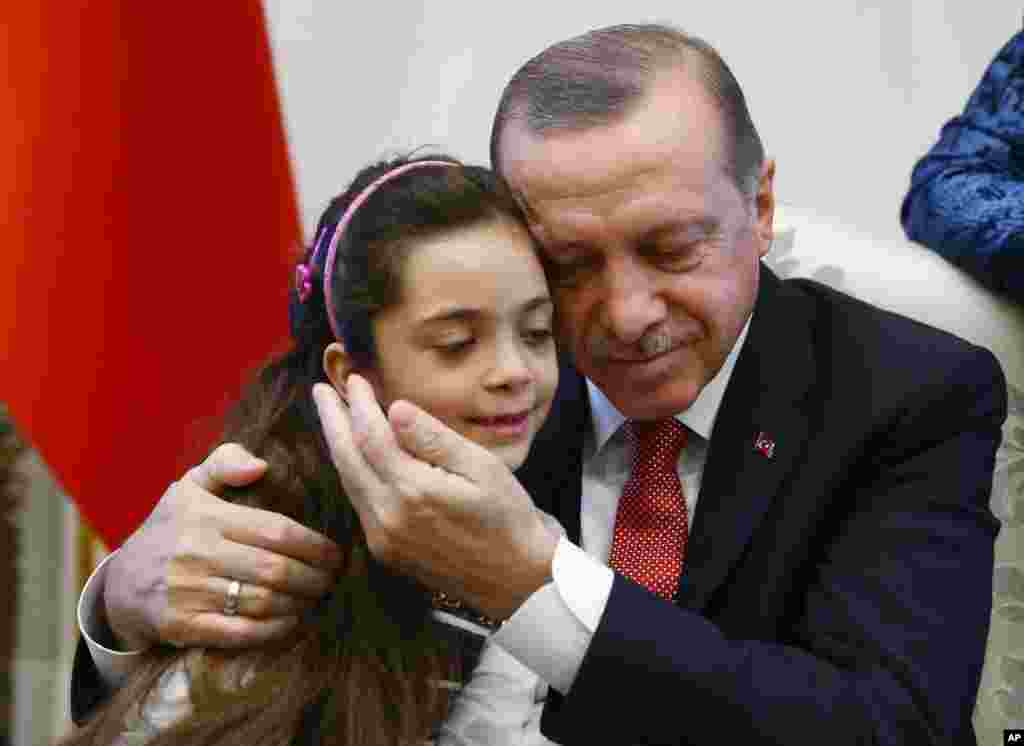 Turkey's President Recep Tayyip Erdogan, embraces Bana Al-Abed, 7, from Aleppo, Syria, at his Presidential Palace in Ankara. Tweets of life under siege in Aleppo by Bana went viral.